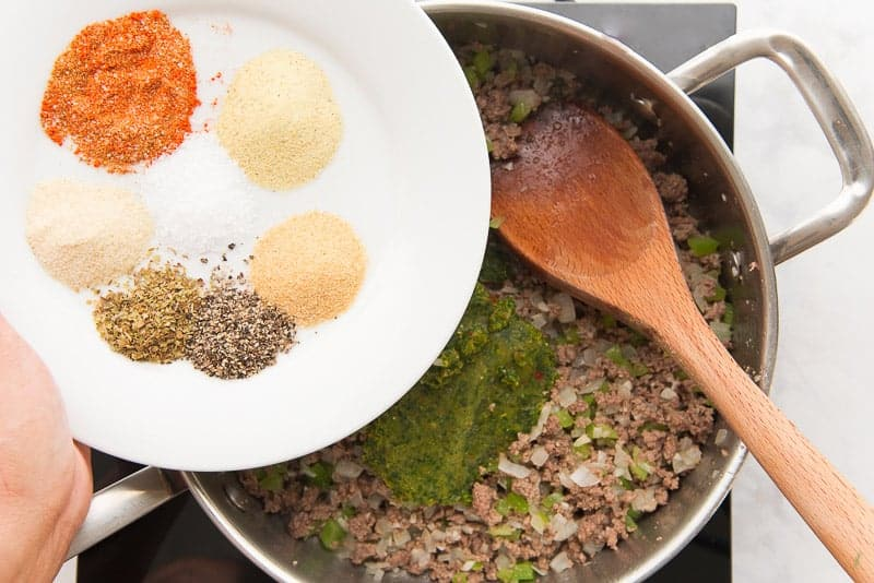 Spices and sofrito are added to a silver pan before being stirred in with a wooden spoon