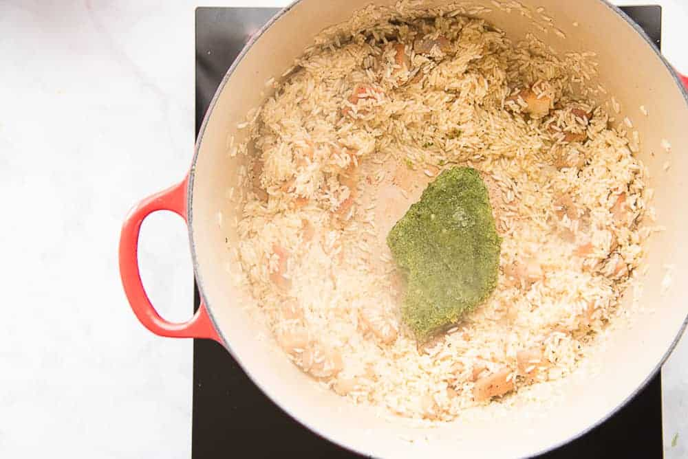 A chunk of sofrito is added to the rice and meat in the pot