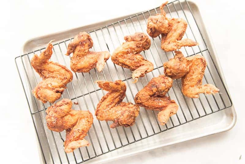 The fried chicken is left to drain on a black rack over a silver sheet pan.