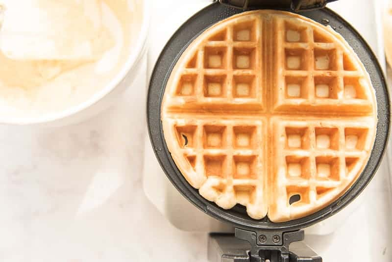 A waffle is finished and ready to be removed from a black waffle iron. The rest of the waffle batter is in a white bowl to the left