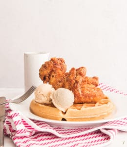 Chicken and Waffles with two scoops of Maple-Cinnamon Butter on a white plate over a red and white striped towel