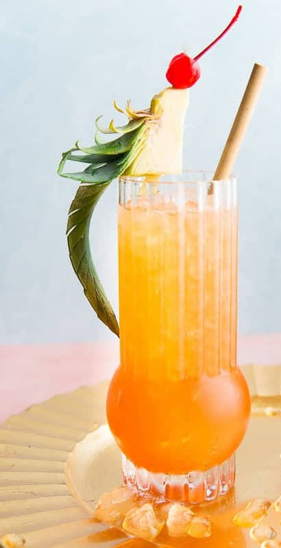 A tall highball glass of Jungle Bird cocktail with a pineapple and cherry bird garnish