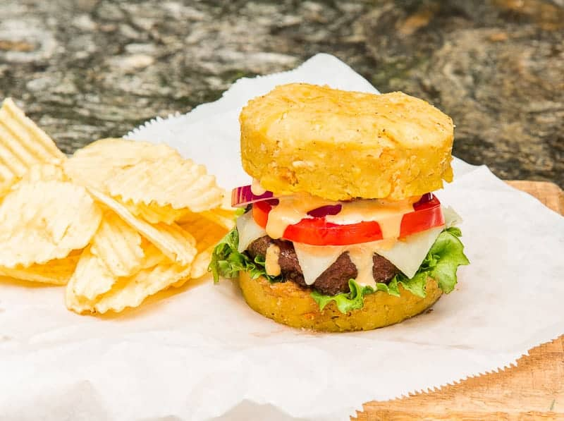 The finished Mofongo Burger on a white sheet of paper next to a stack of chips