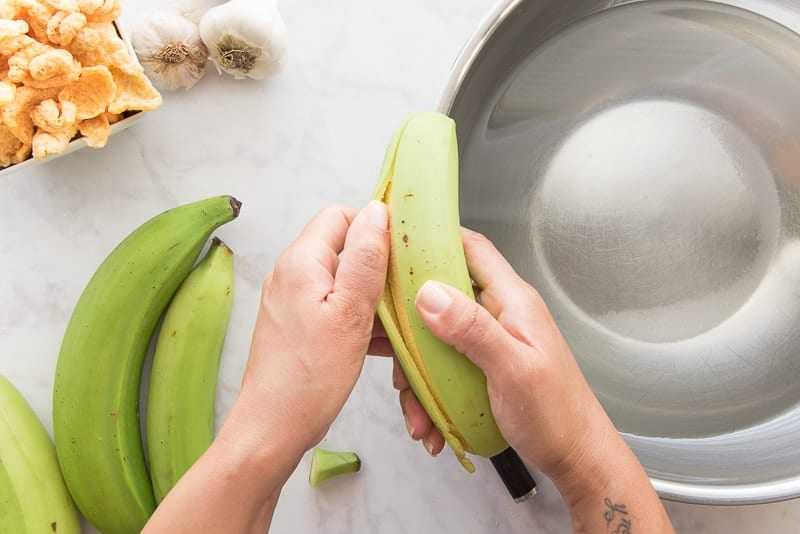 A hand peels the green plantains over a silver bowl filled with salt water.