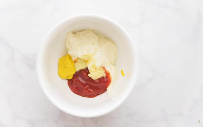 The ingredients used to make the burger sauce for the Mofongo Burgers- mayo, ketchup, mustard, garlic, and adobo- are in a white ceramic bowl.