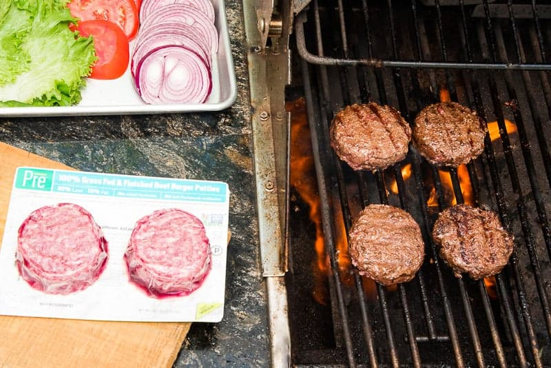 Four burgers are grilling on a grill. To the left of the grill is a wooden platter with a pack of uncooked burgers. Above the platter is a metal pan with lettuce, onions and tomatoes on it.
