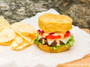 A Mofongo Burger topped with lettuce, tomato, onions, cheese and burger sauce