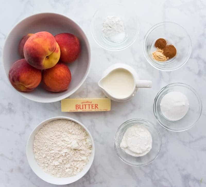 The ingredients needed to make Old-Fashioned Peach Cobbler: peaches, baking powder, salt, spices, sugar, cornstarch, butter, cream, and flour