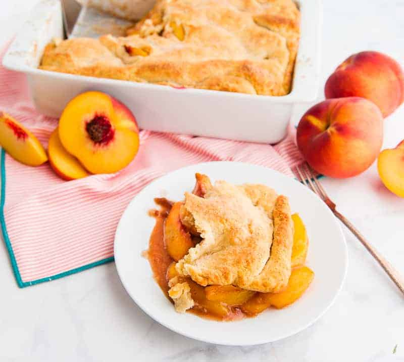 A serving of Old-fashioned Peach Cobbler on a white plate. The baking dish of peach cobbler is in the background next to peaches.