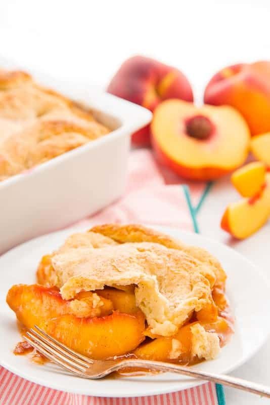 A portrait of a serving of Old-Fashioned Peach Cobbler on a white plate with a silver fork
