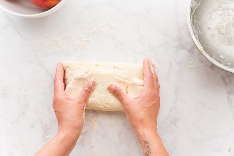 Hands fold the dough to laminated it.