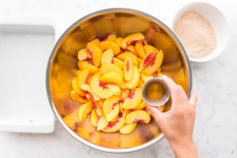 A hand holds a jigger of bourbon over the bowl of sliced peaches
