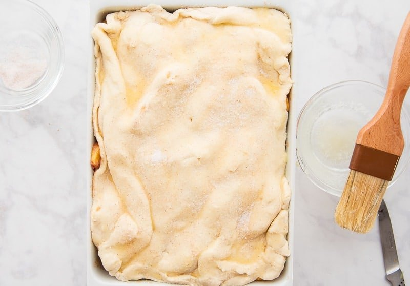 The dough is brushed with melted butter and sprinkled with cinnamon-sugar before baking