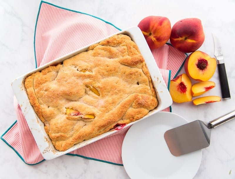 The baked Peach Cobbler is in a white baking pan next to a white plate with a silver server propped on it. Two peaches and a peach half are in the top right corner.