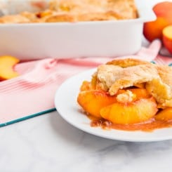 A serving of Old-fashioned Peach Cobbler on a white plate. Peach halves are in the background