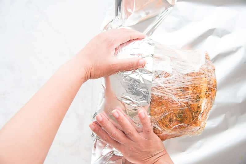 Two hands wrap the pork shoulder in foil after it's wrapped in plastic film