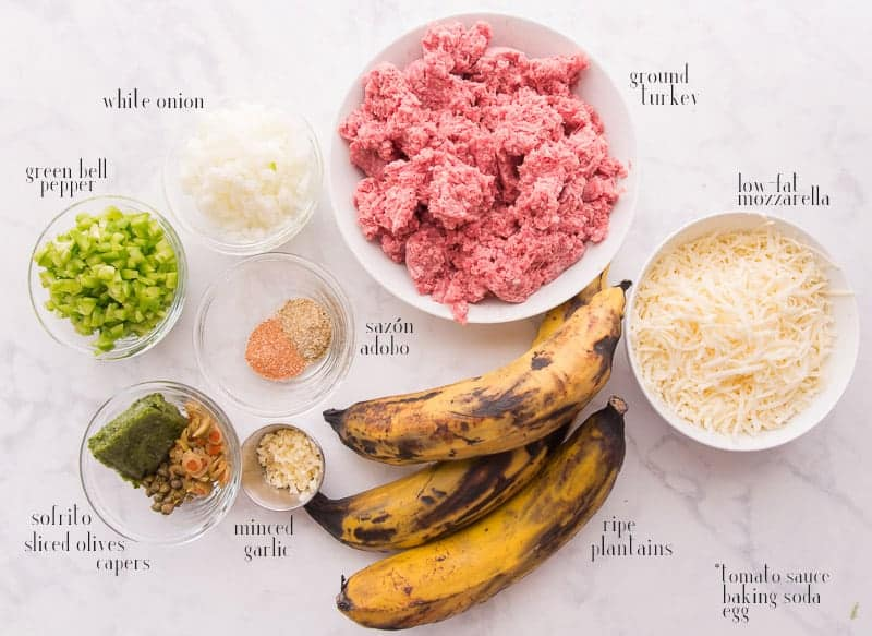 Pictured ingredients to make pastelón: ground turkey, shredded mozzarella, ripe plantains, spices, green peppers, onions, garlic, capers, olives, and sofrito.
