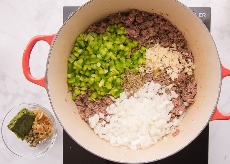 Diced green pepper, onions, and mince garlic is added to ground meat in a red pot.