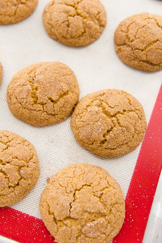The brown cookies on a red and white silicone baking mat after being baked. They're slightly cracked and puffy.
