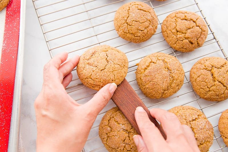 A hand gently pushes the brown Soft Pumpkin Cookie of of a brown flat spatula onto a silver wire rack.