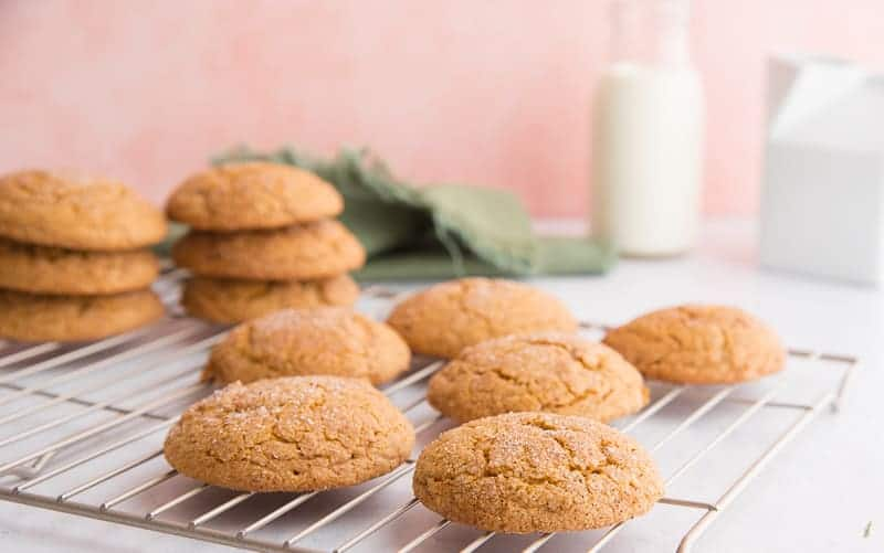 The brown cookies are on a silver wire rack. Two stacks of three cookies are in left background next to them is a green napkin a bottle of milk and white ceramic container.