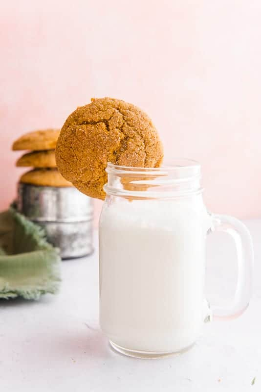 A Soft Pumpkin Cookie is used to garnish a glass mug of milk. In the background is a silver container on which are propped 3 cookies. A green napkin peeks out from the left side.