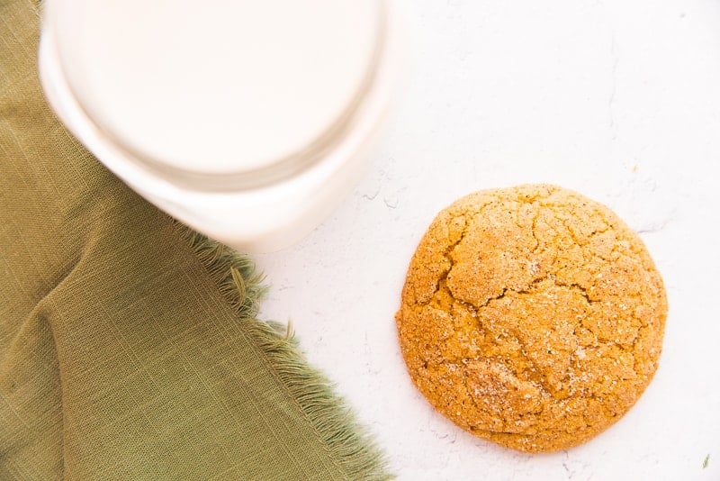 A single Soft Pumpkin Cookie on a white surface next to a green fringed napkin and a glass of white milk.