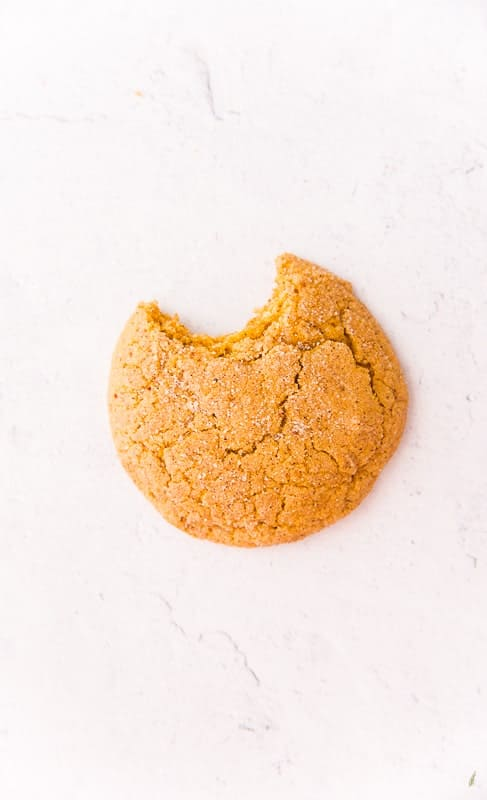 A single Soft Pumpkin Cookie with a bite take out of it is on a white and grey marble surface.