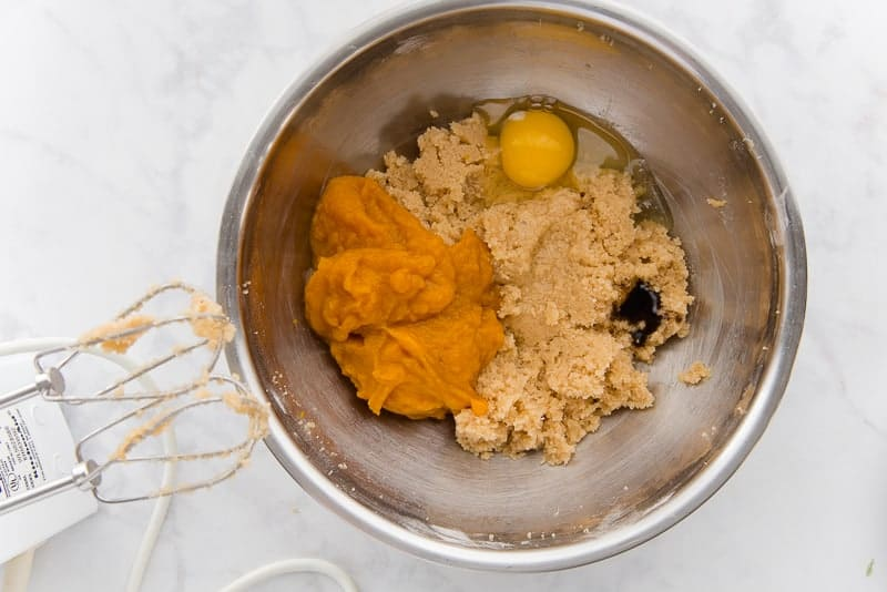 An egg and pumpkin puree are added to the beaten butter and sugar in a silver bowl. The beaters of an electric mixer in the bottom left corner.