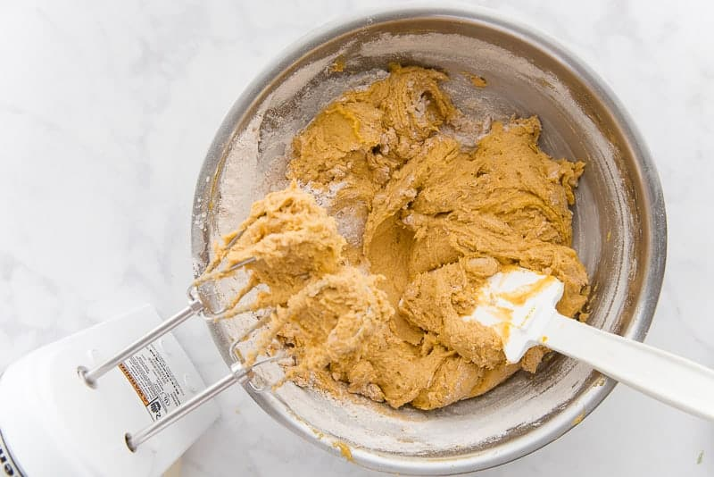 The brown batter is thick after the flour has been added to it. The batter is in a silver mixing bowl with a white spatula sticking out of it. The beaters of a mixer still have dough on it.