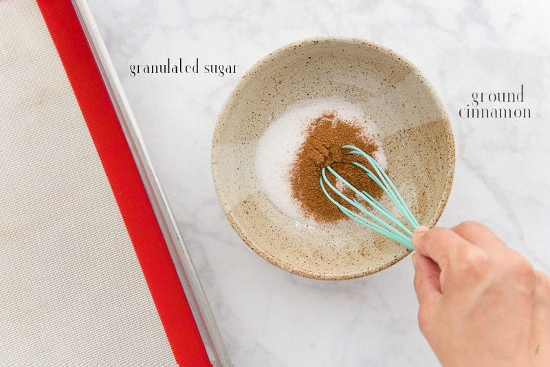 Ground cinnamon is added to white sugar in a cream ceramic bowl. A sheet pan lined with a silicone mat is at left.