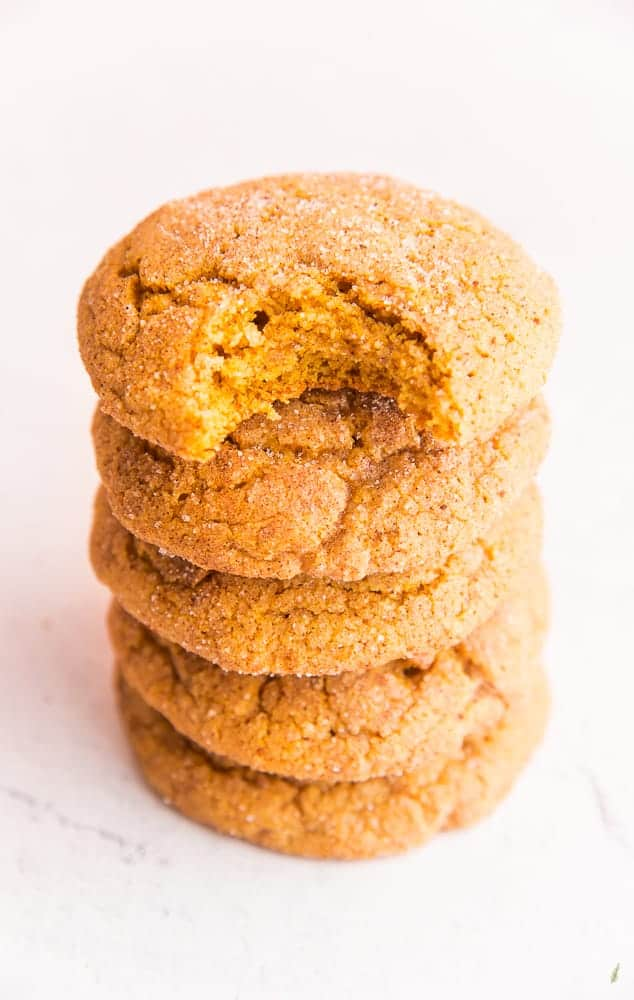 A stack of 5 Soft Pumpkin Cookies on a white marble surface. Top cookie is bitten.