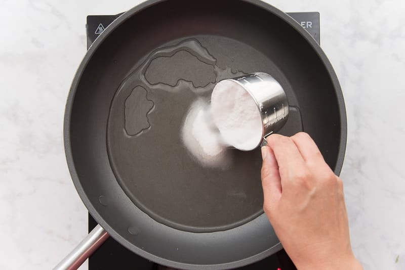 Dark colored pan with water. Brown hand adding white sugar from silver measuring cup.