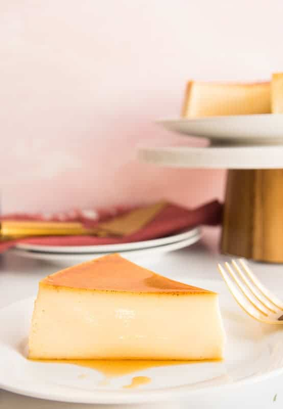 Slice of flan on a white plate. Gold forked propped on left of plate. White plates in background with red napkin and gold server on top.