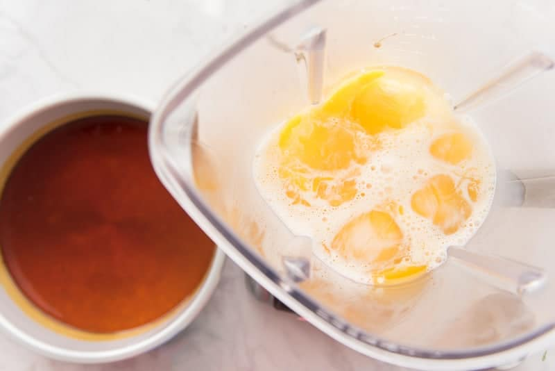 Yellow eggs, white milk, in a clear, plastic blender. Silver pan with amber sugar to the left of the blender