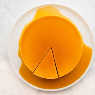 Orange whole flan with a piece cut on a white plate