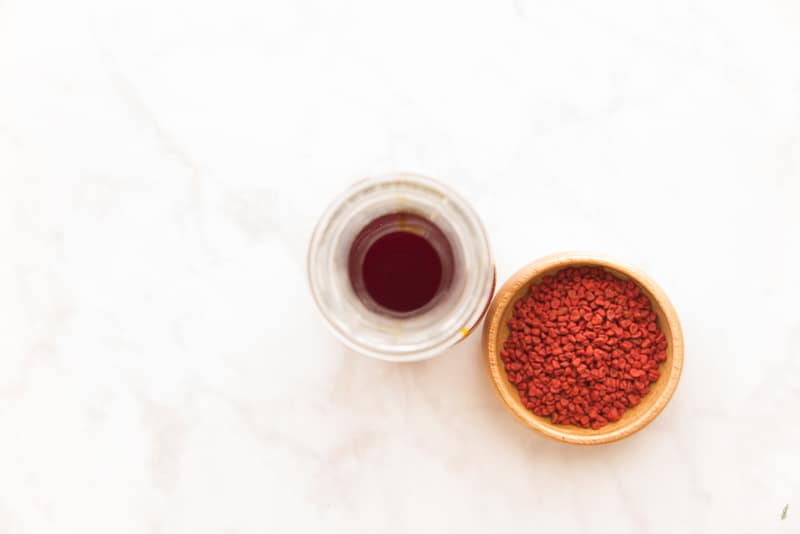 Overhead image of a glass carafe filled with achiote oil next to a wooden bowl filled with achiote seeds