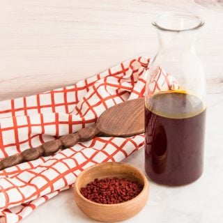 Horizontal image wooden bowl with orange achiote seeds next to a glass bottle half-filled with achiote oil in front of an orange and white windowpane kitchen towel with a wooden spoon on top