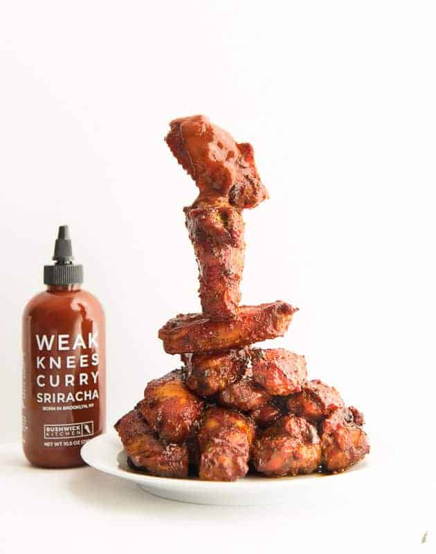 A stack of Curry Sriracha Air Fryer Wings on a white plate next to a bottle of the sauce