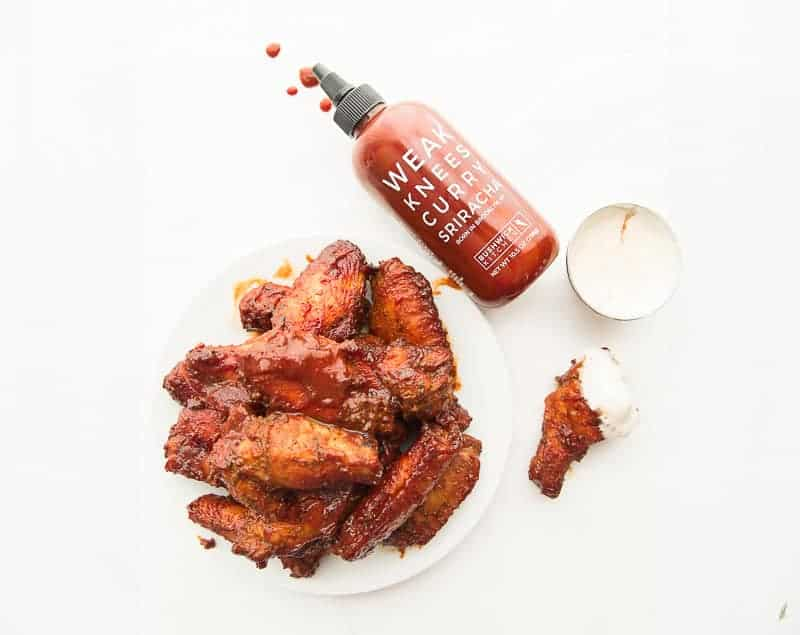 A square image of a plate of Curry Sriracha Air Fryer Wings next to a spilled bottle of sauce and a single wing dipped in dressing from a silver cup above it