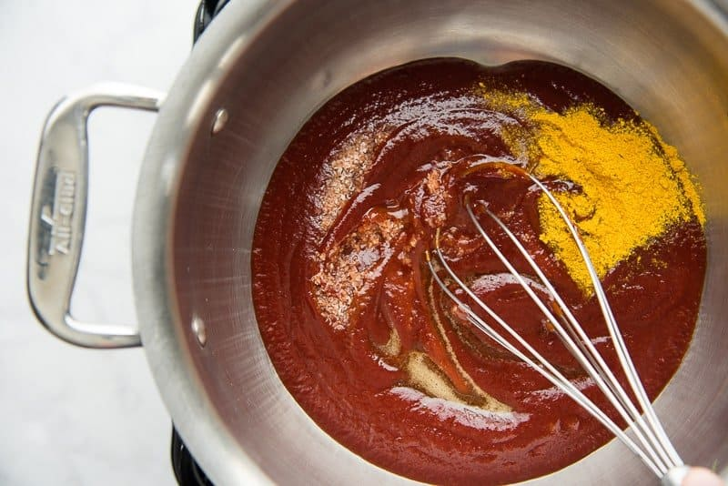 The spices are stirred into the silver pot of sauce with a silver whisk