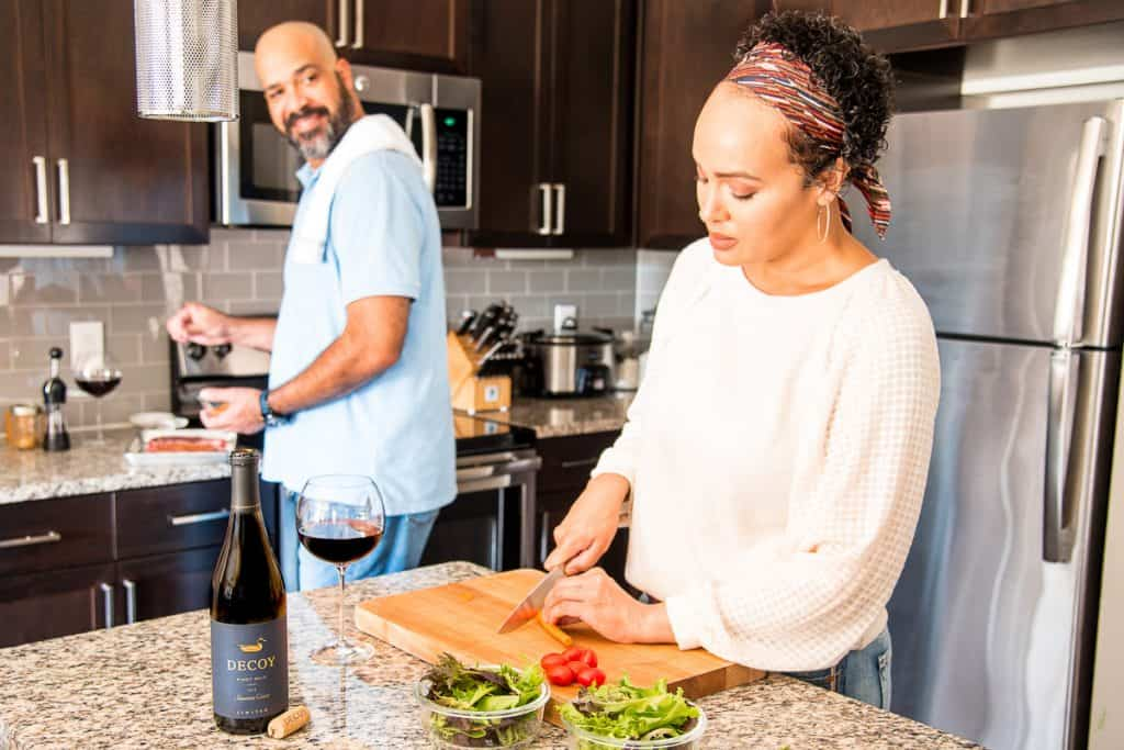 Date Night begins with both partners chipping in. Woman in white sweater chopping carrots. Man in blue shirt seasoning steak turns to talk. Open bottle of Decoy Wine in foreground
