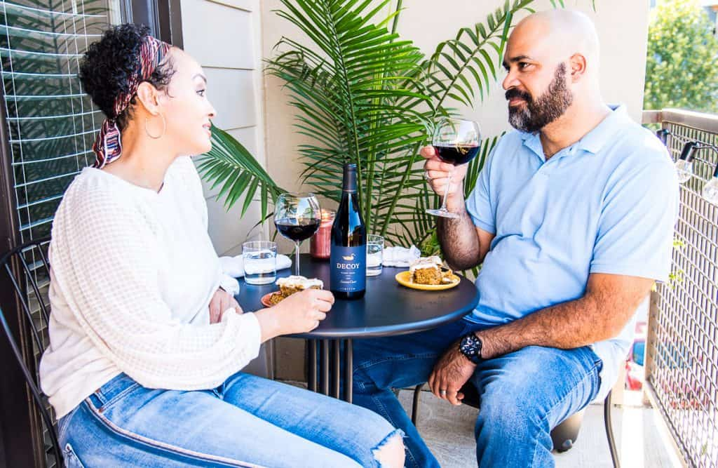 A couple closes Date Night with dessert and glasses of red wine.