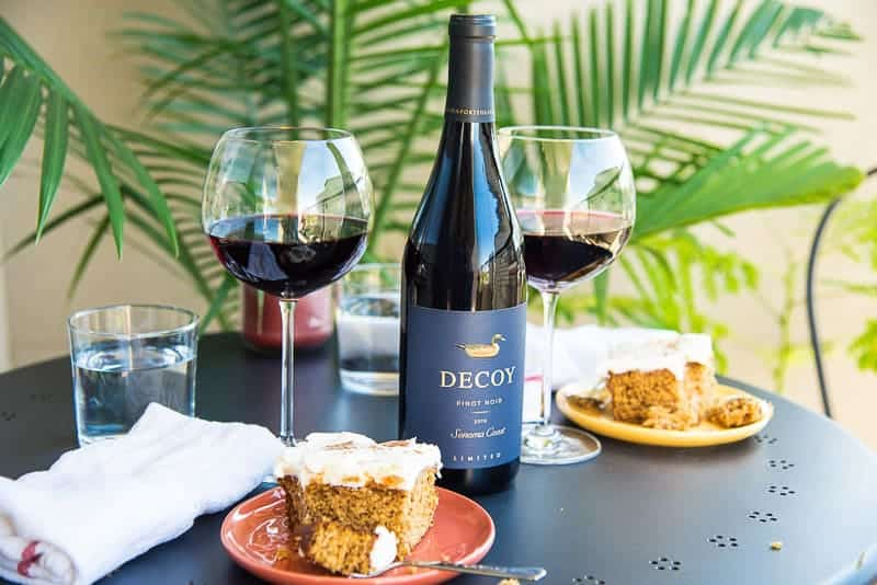 Date Night comes to a close. A bottle of red wine on a black table surrounded by glasses of red wine and plates with pumpkin cake.