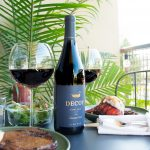 A bottle of Decoy wine sits on a black table in between two glasses of wine and two green plates with a steak and lobster tail on each.