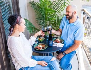 A couple sits at a cafe table on a balcony and toasts over surf and turf dinner