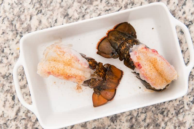Two lobster tails in a white baking dish are butterflied open.