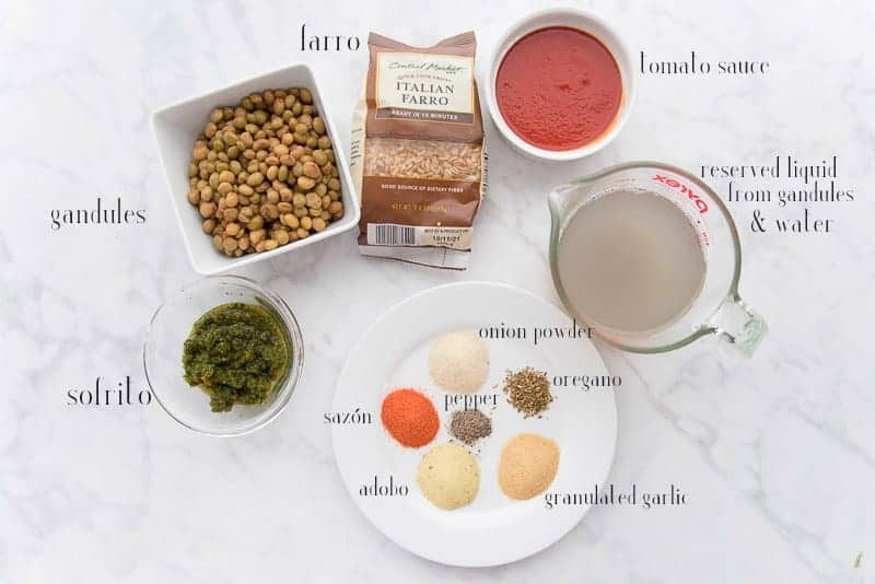 Ingredients to make farro are on a white surface: a square, white bowl of drained gandules, a bag of farro, a white ramekin of tomato sauce, a cup of liquid, a white plate of spices, and a glass bowl of sofrito
