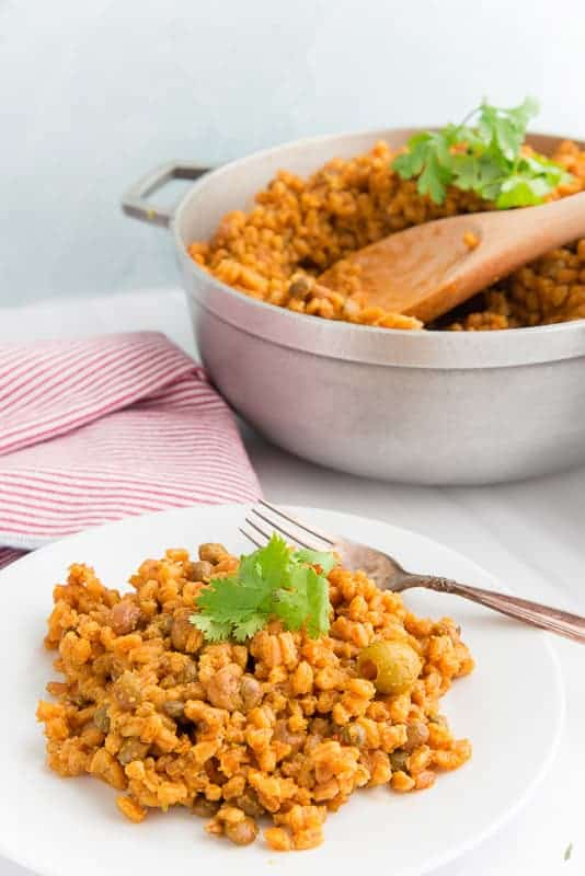 A white plate with farro-z con gandules on it. A silver fork on a white plate. A Silver pot with more farro-z in it and a wooden spoon sticking out of it.