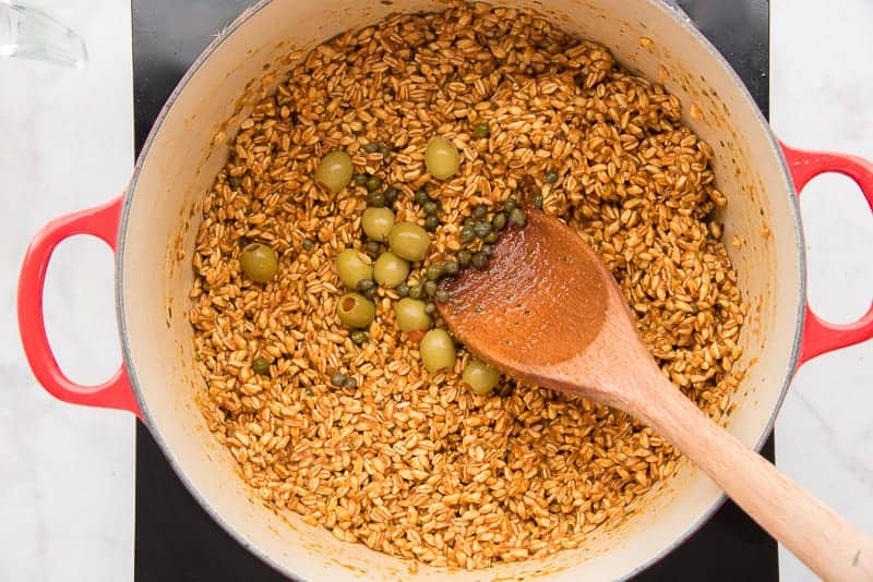 A pot of farro with a wooden spoon stirring in olives and capers